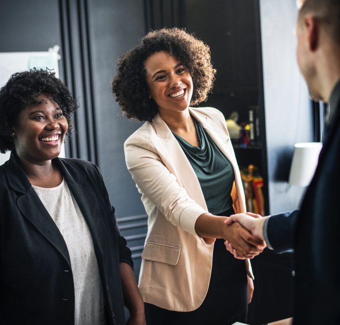 Woman smiling while handshaking a man