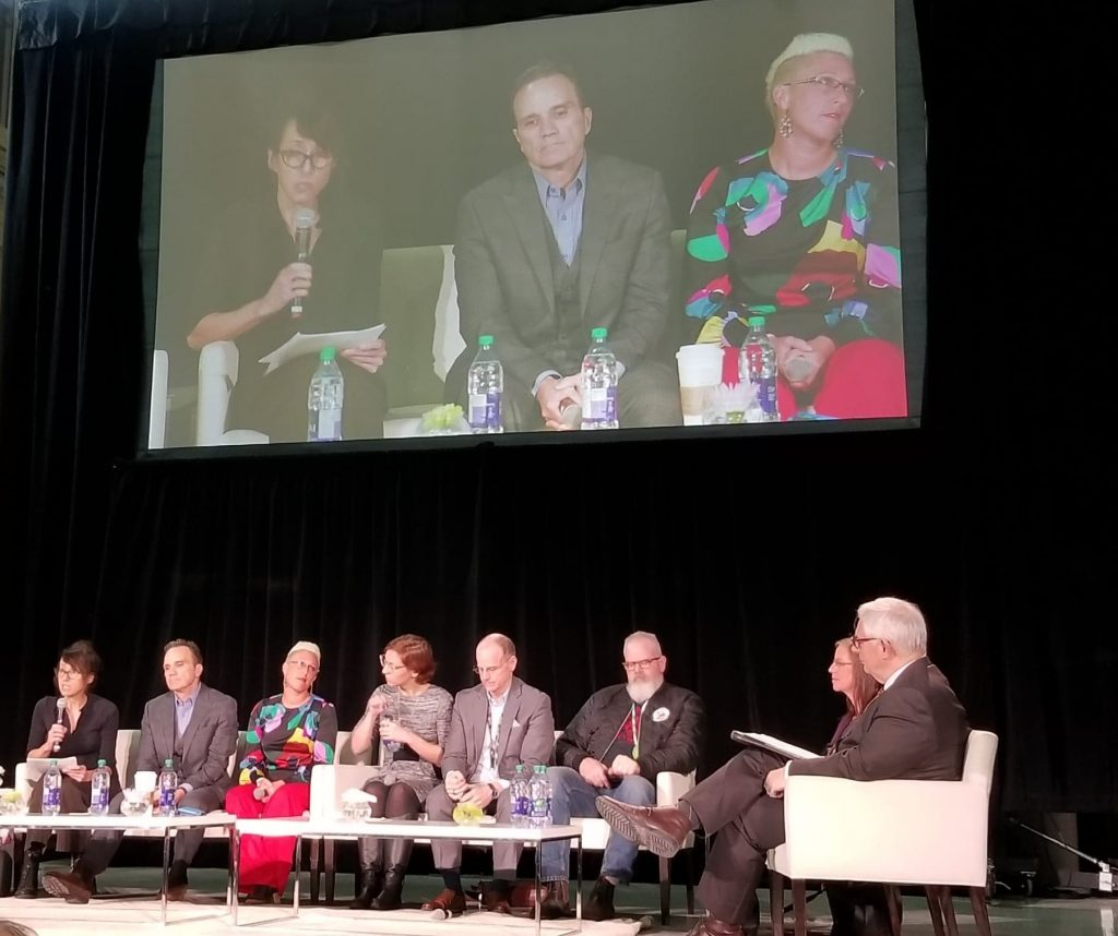 Image shows the stage and panel of Dr. David Barnard and 9 guest professional speakers on Addictions.